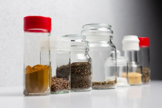 白い表面のガラスカップの異なる調味料。