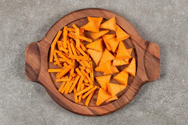 Chip di forma diversa sulla tavola di legno su grigio.