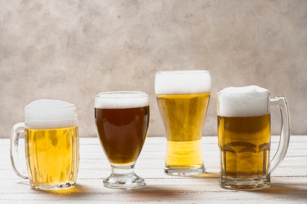 Different shape of glasses with beer on table