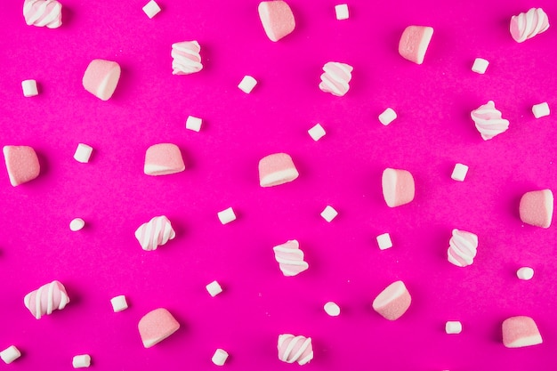Different shape of marshmallows on pink background