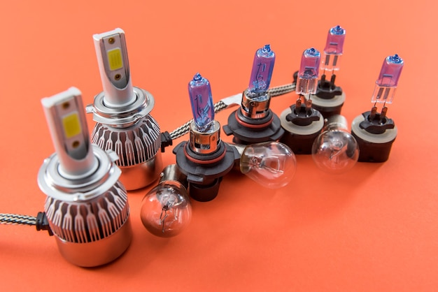 Different shapes and sizes car light bulbs isolated on orange. modern auto glass lamp. energy power
