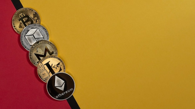 Different shining cryptocurrency coins, crypto currency on yellow and red background with copy space for text.