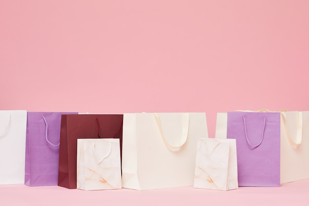 Different shopping paper bags isolated on pink background
