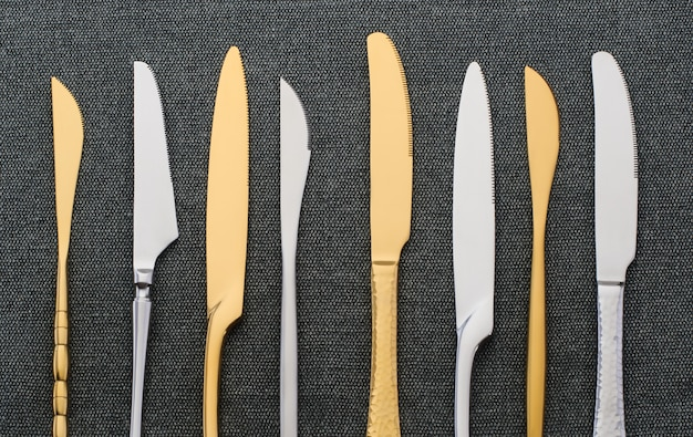 Different silver and gold knives on a black napkin