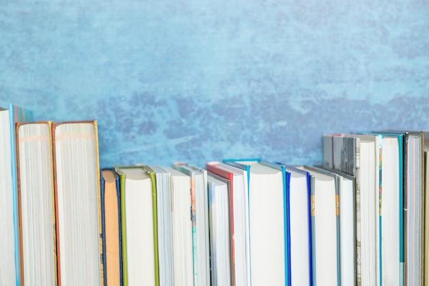 本棚、青い背景に異なるサイズの本。教育、知識、読書、学校のテーマに戻る。