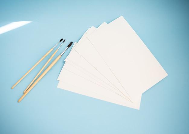 さまざまなサイズの水彩ブラシは、青い背景に水彩紙と一緒に横たわっています。描画レッスン。