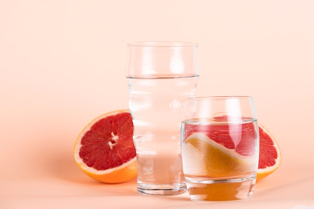 Different sized glasses of water with red oranges