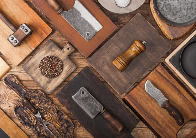 肉の手斧、フォーク、ナイフ、その他の道具を備えた木製の背景にさまざまなサイズと形状のキッチンまな板。