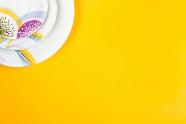 Разные размеры пустых тарелок, ярко-желтый фон, копия пространства