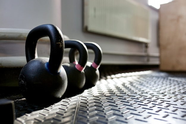 Different sizes of kettlebells weights lying on gym floor