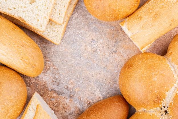 大理石の背景に、さまざまなスライスパンと全粒粉パン。