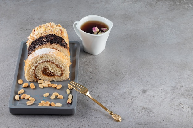Different sliced roll cake on a wooden plate next to a cup of tea on the marble surface