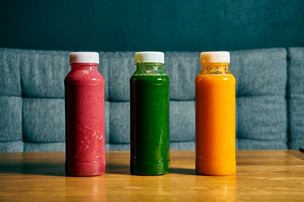 Different smoothies in bottles. set of cherries, spinach and orange smoothie on a wooden table. detox, healthy drink