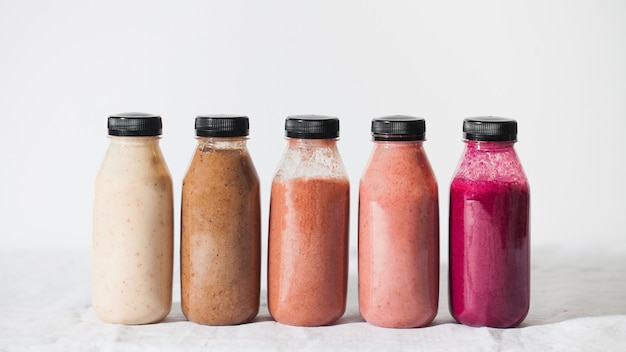 Different smoothies bottles on a white background.