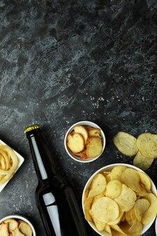 黒のスモーキーな表面にさまざまなスナックとビールのボトル