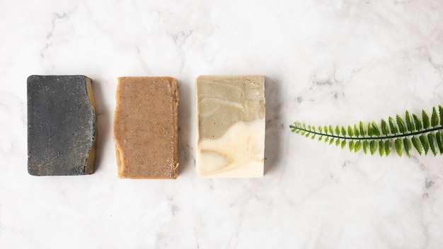 Different soaps for skincare next to green leaf