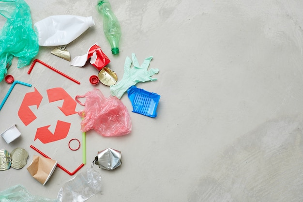 灰色の背景に分離されたリサイクルシンボルの周りにある別の種類のゴミ