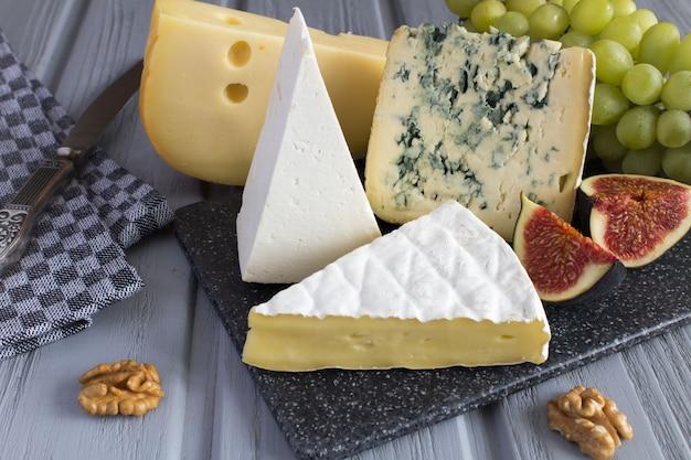 灰色のまな板にさまざまな種類のチーズとフルーツ