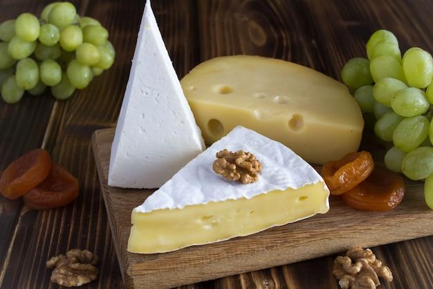 さまざまな種類のチーズ、ブドウ、茶色のまな板にドライアプリコット
