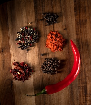 Different sorts of pepper on a wooden background