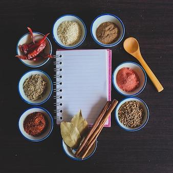 背景にタイ料理を調理するためのノートブック付きの小さなボウルにさまざまなスパイスとハーブ。