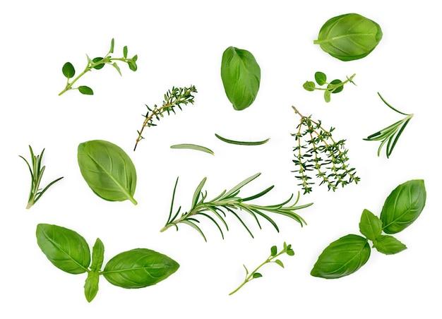 白い表面、バジルの葉、タイム、ローズマリー、上面図で分離されたさまざまなスパイスとハーブ。高品質の写真