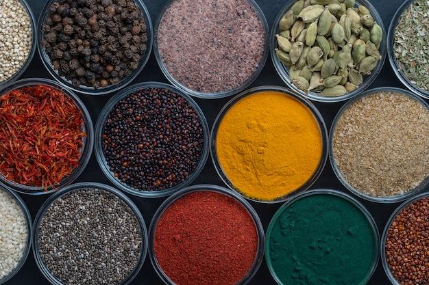 背景にさまざまなスパイスやハーブ、クローズアップ、上面図。食品を調理するための色とりどりのスパイス、種子、ハーブの品揃え