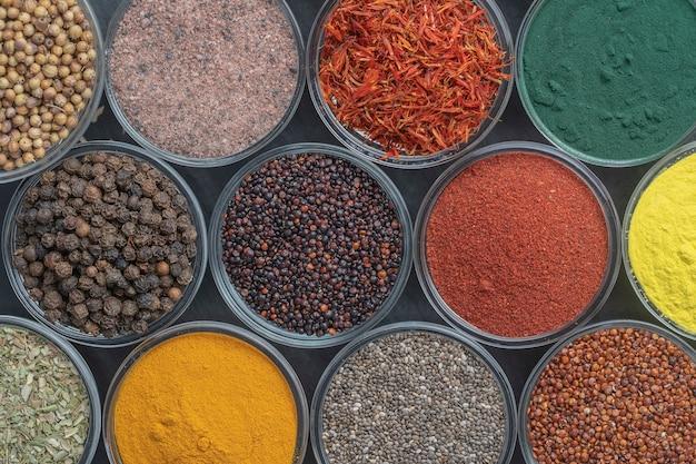 テーブルの上のさまざまなスパイスとハーブ、クローズアップ、上面図。食品を調理するための色とりどりのスパイス、種子、ハーブの品揃え