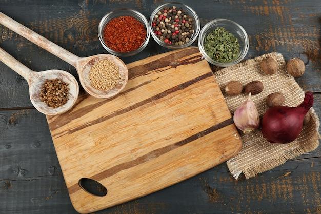 色の木製テーブルにまな板とさまざまなスパイスやハーブ