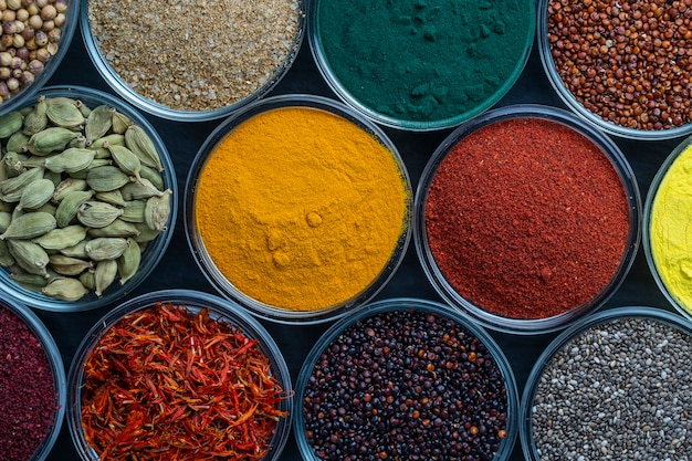 Different spices and herbs on background close up top view