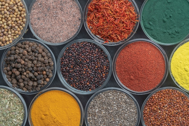 Different spices and herbs on table, close up, top view. assortment colorful spices, seeds and herbs for cooking food
