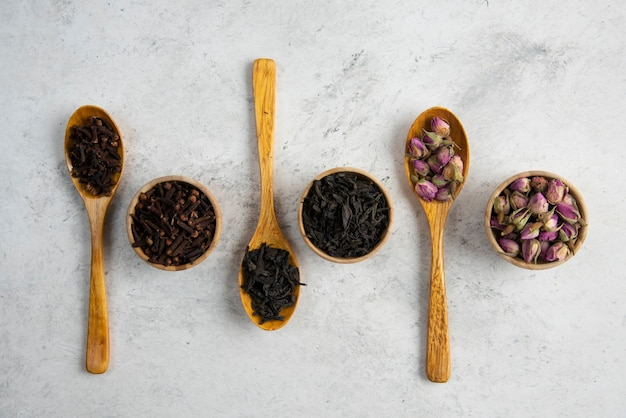 Spezie differenti in cucchiai e ciotole di legno.