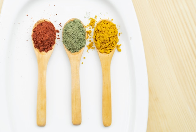 Different spices on wooden spoons