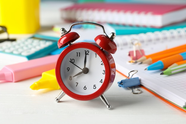 Different stationary and alarm clock on white wooden table, close up