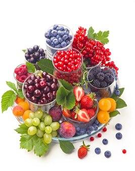 Различные летние ягоды красной смородины, крыжовника, малины в стеклянных лотках