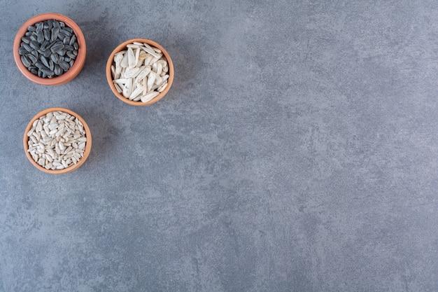 Diversi semi di girasole in ciotole, sulla superficie blu
