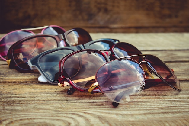 Different sunglasses on wooden background. reflection of clouds and trees in sunglasses.