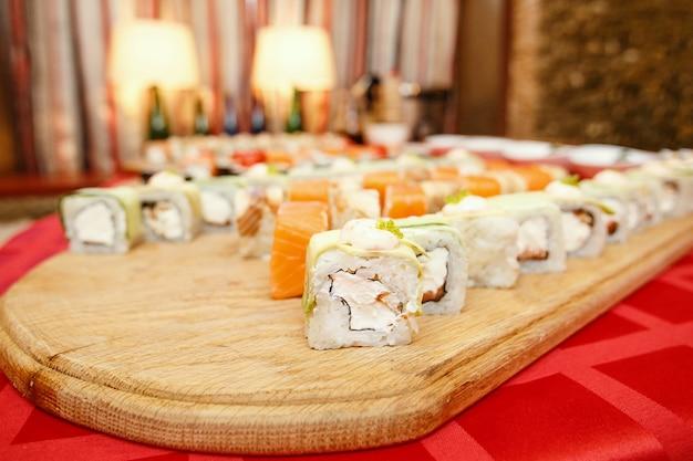 木の表面の皿にわさびと生姜をセットしたさまざまな巻き寿司