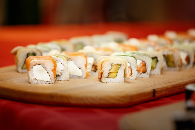 木の表面の皿にさまざまな巻き寿司、わさび、生姜