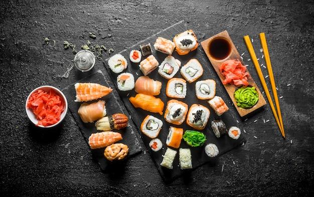 箸でさまざまな巻き寿司。黒い素朴なテーブルの上