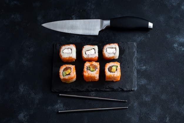 Different sushi served on a black slate plate with japanese knife and metal chopsticks