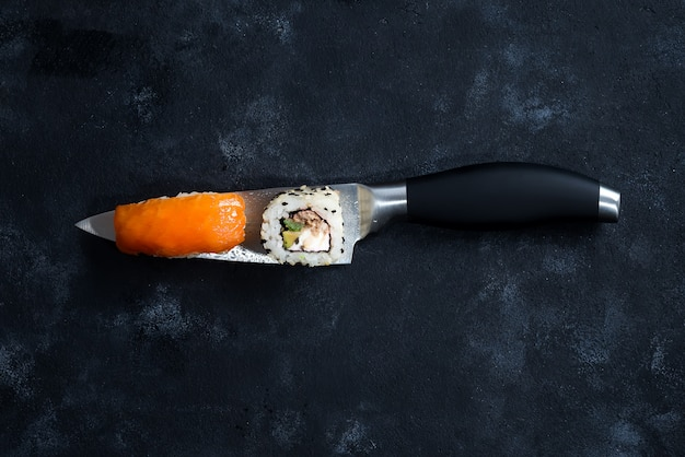 Different sushi served on a japanese knife on a black background .