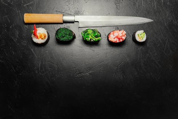 Different sushi with japanese knife on black stone slate background. sushi on a table.