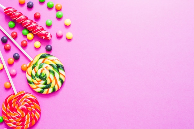 Different sweet candies on pink background
