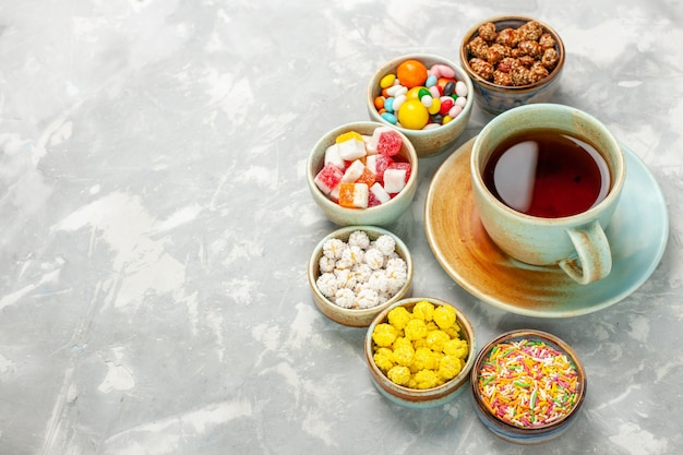 Different sweet candies with marshmallows and cup of tea on white desk