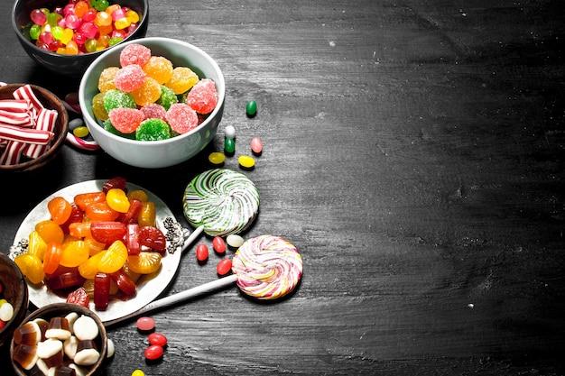 다른 달콤한 사탕, 젤리와 설탕에 절인 그릇에. 검은 칠판에.