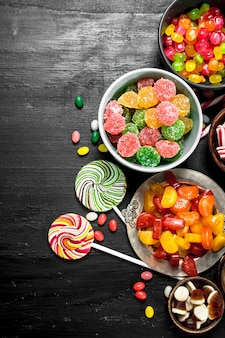 Different sweet candy, jelly and candied in a bowl. on the black chalkboard.