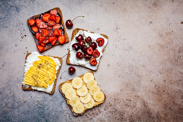 Different sweet fruit toasts with banana, mango, cherry and strawberries on dark background, top view, copy space.