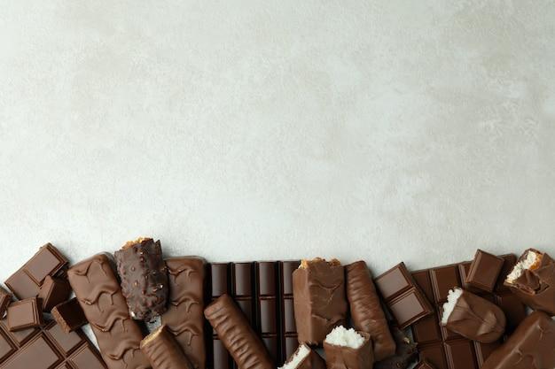 Различные вкусные конфеты на белом текстурированном фоне
