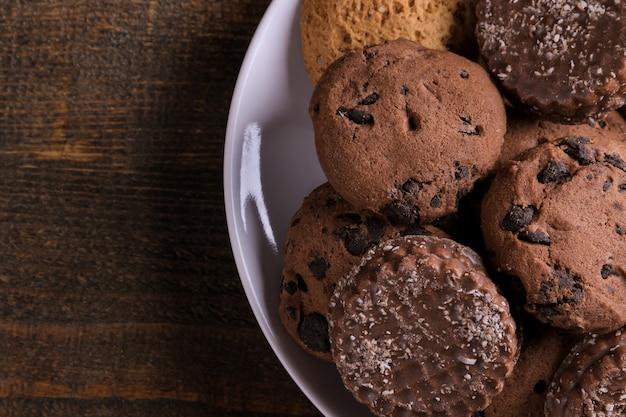 茶色の木製テーブルの皿にさまざまなおいしいクッキー。上面図のクローズアップ